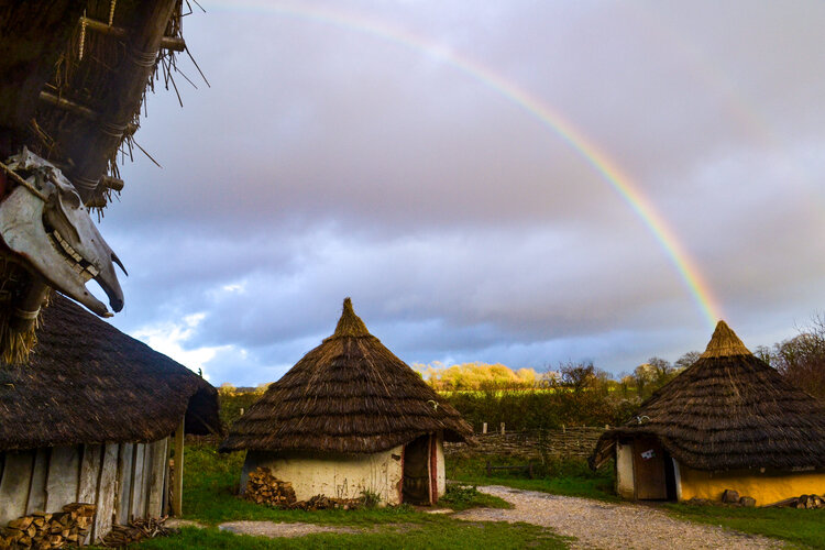 Image of Butser Ancient Farm's iron age roundhouse with a rainbow over it