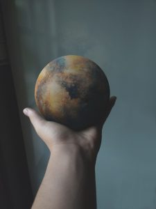 Image of hand holding small planet Earth